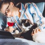 Frau mit Glas Rotwein im Bett vor dem Laptop